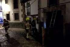 Varios bomberos en la calle, junto a la vivienda del incendio