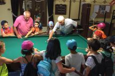 Un socio enseña a los niños a jugar al villar