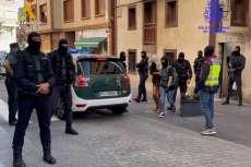Varios guardia civiles con capucha y un vehículo en la calle