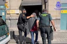 Dos guardia civiles llevando un detenido
